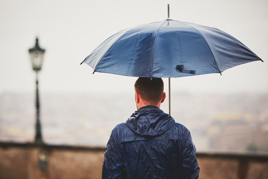 man outside in rain with umbrella
